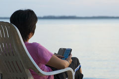 Woman and Smartphone by the Sea Royalty Free Stock Photography