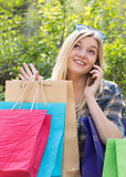 Woman with smartphone and shopping bags Royalty Free Stock Photos