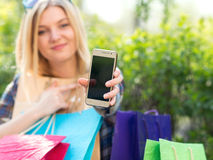 Woman with smartphone and shopping bags Royalty Free Stock Photo