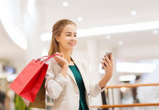 Woman with smartphone shopping and taking selfie. Sale, consumerism, technology and people concept - happy young woman with smartphone and shopping bags taking Royalty Free Stock Photography