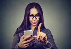 Woman with smartphone showing no attention with finger gesture. Parental control concept. Young woman with smartphone showing no attention with finger hand Stock Photography