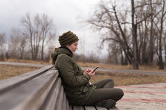 Woman with smartphone sitting on a bench Royalty Free Stock Photos