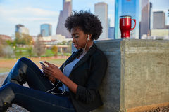 Woman with smartphone sitting in the park Royalty Free Stock Image