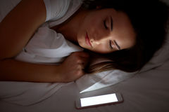 Woman with smartphone sleeping in bed at night Stock Photo