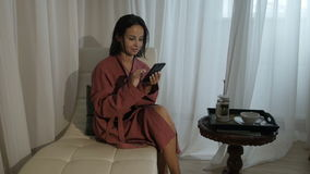 Woman with smartphone after spa. Smiling woman sitting and relaxing with smartphone after spa procedure stock footage