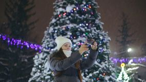 A woman with a smartphone on the square near the Christmas tree, shares photos on social networks.  stock video footage