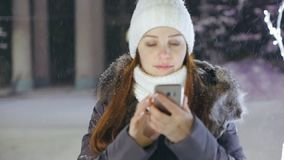 A woman with a smartphone on the square near the Christmas tree, shares photos on social networks.  stock video