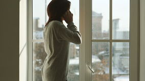 Woman with smartphone standing near wide window. Rear view of young woman in gray cardigan using mobile phone while standing near big window at home. In the stock video