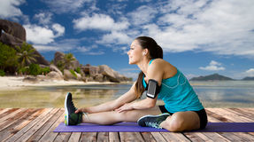 Woman with smartphone stretching leg on mat Royalty Free Stock Photos