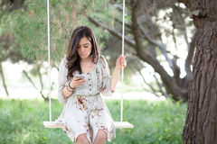 Woman with Smartphone on a Swing Royalty Free Stock Images