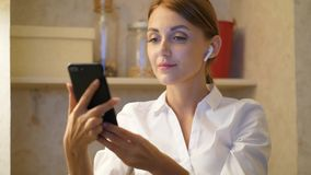 Woman with smartphone take off modern headphones stock video