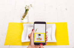 A woman with a smartphone takes pictures of food in a restaurant stock image