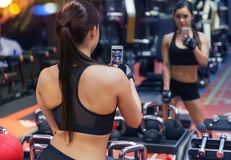 Woman with smartphone taking mirror selfie in gym Stock Image