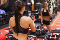 Woman with smartphone taking mirror selfie in gym Royalty Free Stock Photos