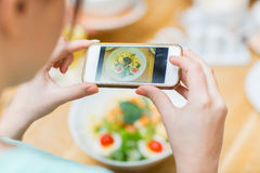 Woman with smartphone taking picture of food Royalty Free Stock Images