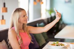 Woman with smartphone taking selfie at restaurant Stock Photography
