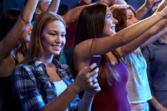 Woman with smartphone texting message at concert Royalty Free Stock Photography