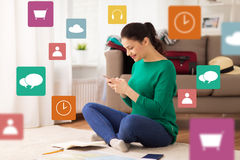 Woman with smartphone and travel map at home. Vacation, tourism, travel and people concept - happy young woman with notebook, passport and map texting on Royalty Free Stock Images