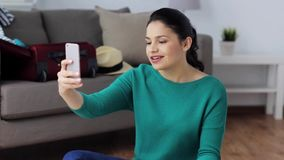 Woman with smartphone and travel stuff at home stock video