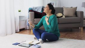 Woman with smartphone and travel stuff at home. Vacation, tourism, travel and people concept - happy young woman with smartphone having video chat at home stock video footage