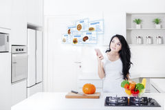 Woman with a smartphone and virtual recipes Stock Photography