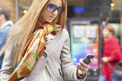 Woman with smartphone walking on street royalty free stock photography