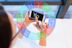 Woman with smartphone and zodiac signs at office. Astrology, horoscope, people and technology concept - close up of young woman in eyeglasses with smartphone and royalty free stock photography