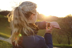 Woman with smartwatch an Back light in a Park Stock Image