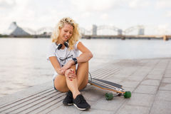 Woman with smartwatch on her wrist and longboard. Modern woman with smartwatch on her wrist and longboard Stock Photos