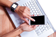 Woman with smartwatch using smartphone Stock Image