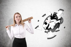 Woman smashed alarm clock drawn on concrete wall. Businesswoman with blond hair has shuttered alarm clock drawn on concrete wall with baseball bat. Concept of Royalty Free Stock Photography