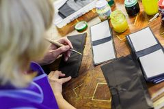 Woman smearing with glue a part of a wallet. Blonde woman in blue unform smearing with glue a part of a wallet. manufacturing process. jars on the background Stock Photos