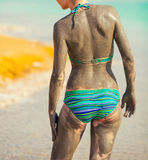 Woman smearing mud mask on the body Royalty Free Stock Photography