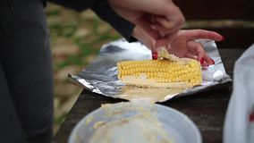 A woman smears corn with oil and spices to bake in foil over a fire. Hands and corn close-up. Motion shooting on the table
