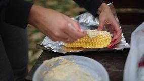 A woman smears corn with oil and spices to bake in foil over a fire. Hands and corn close-up