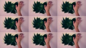 Woman smears draws green paint on white surface. Man draws a green paint smears his hands stained with green paint on the white surface. Multicam split screen stock footage