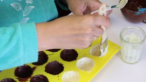 A woman smears a silicone mold to make candies glazed with chocolate with melted white chocolate. Nearby is almonds for the fillin. G stock footage