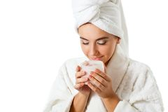 Woman smell jar with scrub. Beautiful woman holding jar with scrub over white background Royalty Free Stock Photography