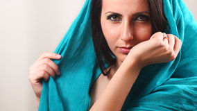 Woman smelling arm wrist. Beautiful young woman with shawl around head smelling her arm-wrist Stock Photography