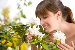 Woman Smelling Blossom Of Rhododendron Flower Stock Photo