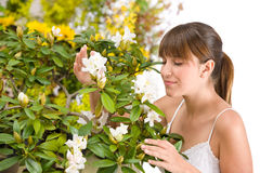 Woman Smelling Blossom Of Rhododendron Flower