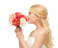Woman smelling bouquet of flowers Royalty Free Stock Photos