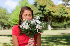 Woman smelling a bunch of flowers while standing in a park Stock Images