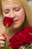 Woman Smelling a Bunch of Red Roses Royalty Free Stock Photos