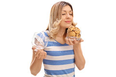 Woman Smelling Cookies In A Jar Royalty Free Stock Photos