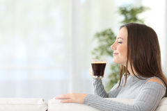 Woman smelling a cup of coffee at home Stock Photo