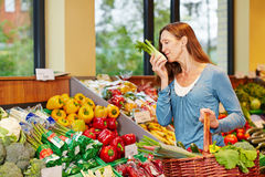 Woman smelling fennel in supermarket Stock Images