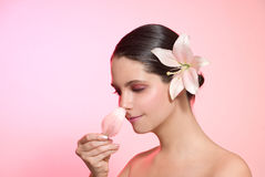 Woman smelling flower. Pretty woman smelling petal fragrance over pink background Royalty Free Stock Photos