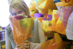 Woman smelling flower bouquet beside shop display in florists, face obscured, portrait Stock Images