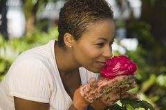 Woman Smelling Flower In Garden Royalty Free Stock Images